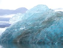 Big piece of blue ice melting. Big blocks of blue ice of a glacier floating on the water with a gray sky and the glacier on the background stock photography