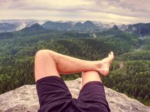 Big bloody callus on man`s heel. Closeup of man feet relax. On rocky summit at edge. Man enjoy view into country royalty free stock images