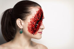 Big bloody wound. Pretty woman wound knife splinter in the skin, bloody part of face. Perfect idea for advertisement, banner, Halloween party card. Cosplay idea Royalty Free Stock Photography
