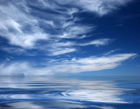 Big blue deep ocean. Ocean and brilliant atmosphere with incoming white clouds. Water like a mirror with long peace-full waves Royalty Free Stock Photography