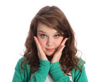 Big blue eyes of surprised brunette teenager girl. Surprise expression of beautiful young teenager girl with big blue eyes wide open and hands raised to her face Stock Image