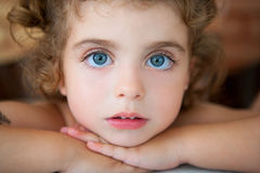 Big blue eyes toddler girl looking at camera. Relaxed Stock Photo