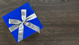Big blue gift box with grey bow on wooden background Royalty Free Stock Photo