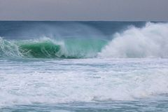 Big blue and green wave of stormy sea with cloudy sky in Barra da Tijuca Rio de Janeiro Brazil. Concept of climatic nature. royalty free stock photography
