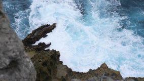 Big Blue havsvågor gör vitt skum och att krascha på för att vagga kustklippan på den tropiska ön längd i fot räknatbakgrund för l stock video