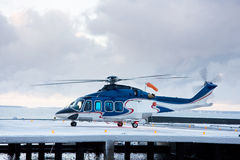 Big blue helicopter. A photo of passenger helicopter in the snow blizzard taking off from the platform Royalty Free Stock Photos