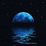 Big blue moon reflected in water Stock Image