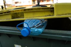Big blue plastic bottle in a yellow green trash bin - Recycle for nature stock photos