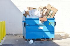 Recycle dumpster bin with all types of recyclable materials. A big blue Recycle dumpster bin holding large amounts of paper cardboard and all types of recyclable Stock Photo