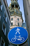 Big blue road sign and Basilica. Pedestrian and cycling zone sign with Saint Peter's church on background. Riga, Latvia stock photography