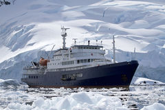 Big blue tourist ship in Antarctic waters against the backdrop o Royalty Free Stock Images
