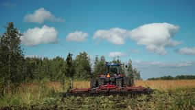 Big blue tractor harrows field near a birch forest, back view.  stock footage