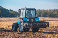 Big blue tractor plows the field and removes the remains of previously mown corn. Part of the cultivator, steel, round discs in a row close-up. Work Stock Images