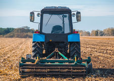 Big blue tractor plows the field and removes the remains of previously mown corn. Part of the cultivator, steel, round discs in a row close-up. Work Royalty Free Stock Image