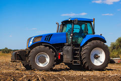 Big blue tractor plows the field and removes the remains of previously mown sunflower. Work agricultural, cleaning machines Stock Photography