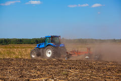 Big blue tractor plows the field and removes the remains of previously mown sunflower. Stock Photo