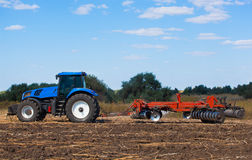 Big blue tractor plows the field and removes the remains of previously mown sunflower. Stock Images