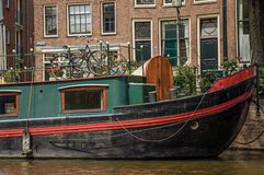 Free Big Boat Moored At Side Of Tree-lined Canal, Old Buildings And Sunny Blue Sky In Amsterdam. Royalty Free Stock Photo - 106882895