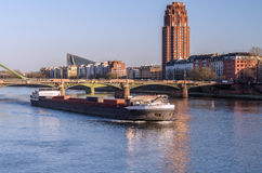 Big boat under the bridge at sunset. Ship flows in the river at sunset time in European city Stock Photography