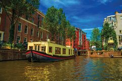 Big boat used as house moored at side of tree-lined canal with old buildings and sunny blue sky in Amsterdam. Famous for its huge cultural activity, graceful Stock Photos