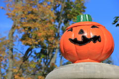 Big,bold color of Jack-O-Lantern. With grinning expression under sunny Fall skies,with gorgeous foliage beyond Royalty Free Stock Images