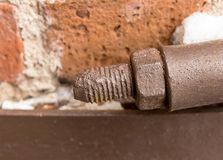 Big bolt with a nut covered with brown paint old design screed on a blurry brickwork background close-up stock image