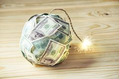 Bomb of money hundred dollar bills with a burning wick. Little time before the explosion. Concept of financial crisis. Big bomb of money hundred dollar bills Royalty Free Stock Photos