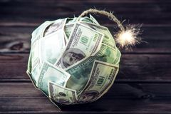 Bomb of money hundred dollar bills with a burning wick. Little time before the explosion. Concept of financial crisis. Big bomb of money hundred dollar bills Stock Image