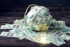 Bomb of money hundred dollar bills with a burning wick. Little time before the explosion. Concept of financial crisis. Big bomb of money hundred dollar bills Royalty Free Stock Photography