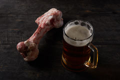 Big bone and beer on a table Royalty Free Stock Photography