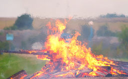 A big bonfire. Large bonfire burning with large logs on the background of the beach Royalty Free Stock Photos