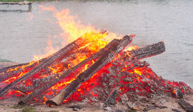 A big bonfire. Large bonfire burning with large logs on the background of the beach Stock Images