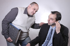 Big boss. Employee disturbing the boss during a call Royalty Free Stock Photography