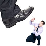 Big Boss. Big Foot kicking tiny businessman Royalty Free Stock Photography