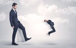 Big boss kicking little employee. Big businessmen kicking himself as a small employee with cloudy background Royalty Free Stock Photo