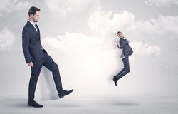 Big boss kicking little employee. Big businessmen kicking himself as a small employee with cloudy background Royalty Free Stock Image
