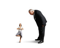 Big boss looking at small meditation woman Royalty Free Stock Photo