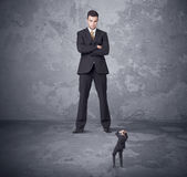 Big boss looking at tiny coworker Royalty Free Stock Image