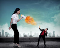 Big boss yelling to her employee with megaphone on fire Royalty Free Stock Photos