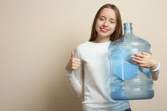 Big bottle. Girl with a big bottle for water on a neutral background Royalty Free Stock Photo