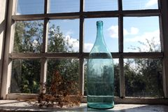 Big bottle at the window. Big bottle of green glass on the window-sill in a country house Stock Image