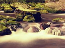 Big boulders covered by fresh green moss in foamy water of mountain river. Light blurred cold water with reflections, white whirlp Stock Image