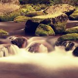 Big boulders covered by fresh green moss in foamy water of mountain river. Light blurred cold water with reflections, white whirlp Stock Images