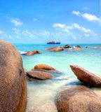 Big boulders at the tropical coastline with turqiouse seawater Royalty Free Stock Photos