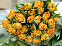 The big bouquet of orange tulips lies on a counter for sale Stock Photo
