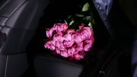 A big bouquet of red roses. The man takes from the car a big bouquet of red roses stock video