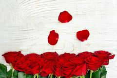 Big bouquet of red roses on white wooden background. Petals.  stock image