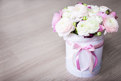 Big bouquet of summer flowers in white round box on wooden table Royalty Free Stock Image