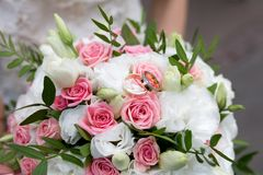 Big flower bouquet. Big Bouquet and Two Wedding Rings. Goods for wedding. This photo is perfect for magazines, shops dealing with wedding dresses ceremonies Royalty Free Stock Photo