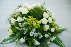 Big bouquet of white roses, yellow daffodils, greenery and lotuses Royalty Free Stock Images
